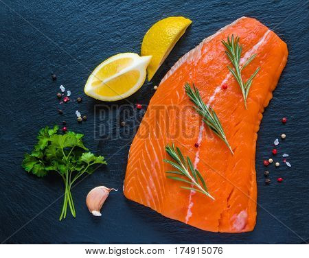 Big piece of raw salmon fresh lemon rosemary and parsley sea salt and pepper on black stone board top view.
