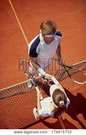 Tennis players shaking hands after training on tennis court