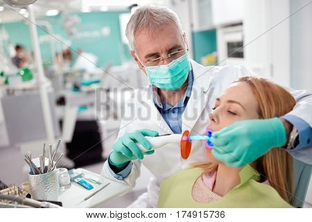 Dentist in dental practice used instrument with light to dry and strengthen dental fillings