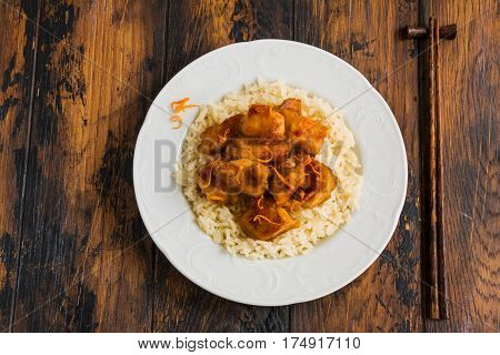 American-Chinese cuisine orange chicken with boiled rice and zest on a white vintage plate and chopsticks wooden table.
