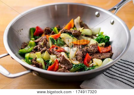 Healthy vegetable & beef stir-fry. Made with flank steak peppers onions and bok choy stir fried in a stainless steel asian wok.