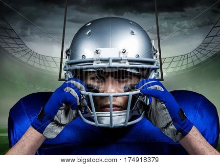 Determined american football player standing against digitally composite stadium
