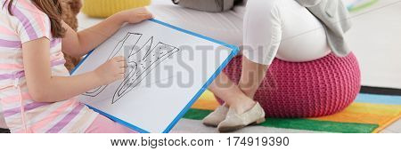 Close-up of girl drawing difficult letter during additional classes at school