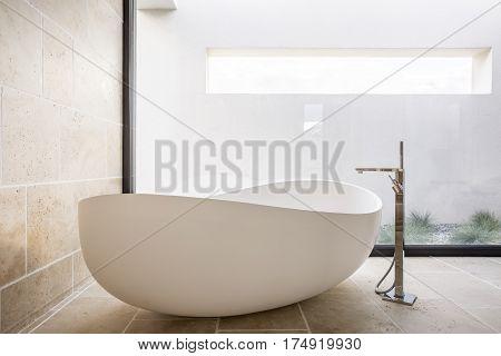 Modern oval bathtub in spacious minimalist bathroom