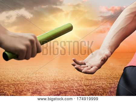 Mid-section of athlete passing the baton to teammate against digitally composite sunset background