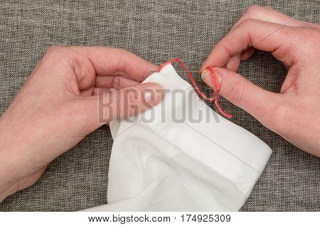 Hands Stitching Orange Yarn On Shirt Sleeve