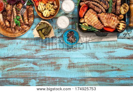 Various grilled food on blue wooden table with copy space grilled steak grilled sausage grilled vegetables and lager beer. Outdoors Food Concept