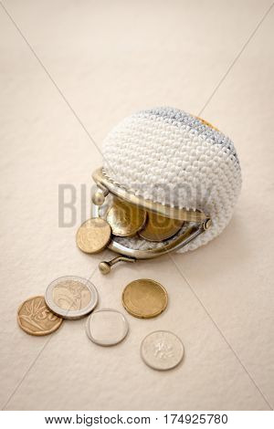 Coins Spilling From A Crocheted Coin Purse