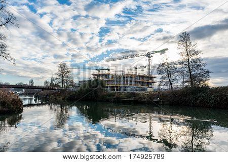 Construction site and cranes next to Nene River, Northampton.