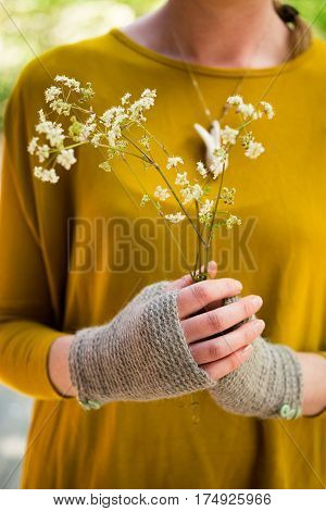 Hands In Knitted Fingerless Gloves Holding A Bunch Of Blooms