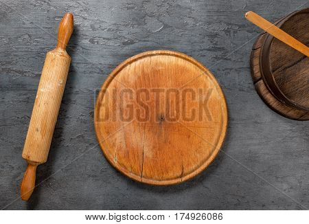 Round blank wooden board with rolling pin and sieve on the dark stone surface top view
