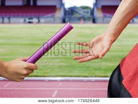 Mid-section of athlete passing the baton to teammate in stadum