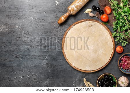 Raw pizza dough with ingredients for cooking vegetarian pizza on the dark stone surface with border top view. Healthy food