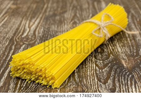 vermicelli spaghetti pasta from durum wheat on wooden background. Concept of healthy food.