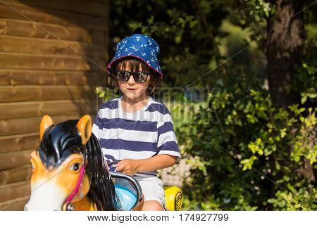 Cute Little Child, Riding On A Horse On A Funfair