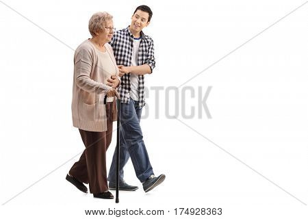 Full length profile shot of an elderly woman with a walking cane walking with a young man isolated on white background