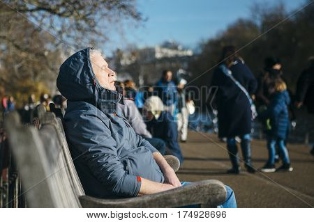 Side view of an old tourist man resting sitting on a bench on a sunny winter day at St James Park in London.