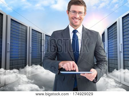 Digitally composite of smiling businessman using digital tablet against server and clouds background