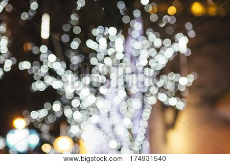 White and purple glitter bokeh lights on a dark background. Useful as an unfocused background. Copy space area available