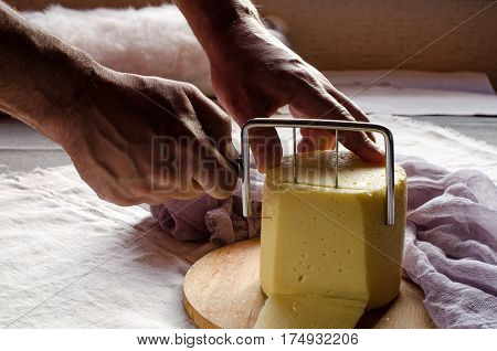 Man Cuts The Cheese On A Wooden Board Closeup
