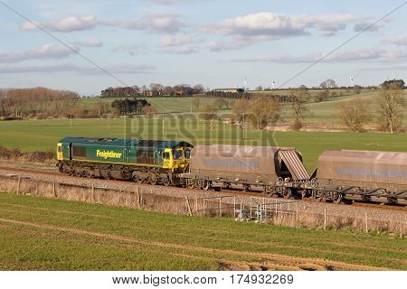 HARROWDEN, UK - MARCH 7: A Freightliner operated stone freight train heads north through Northamptonshire on March 7, 2014 in Harrowden. FLT was founded in 1995 and has an operating revenue of £360Mn