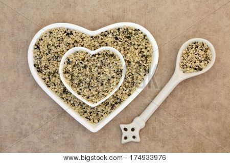 Shelled hemp seed health food in heart shaped china bowl and spoon on natural hemp paper background