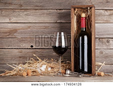 Red wine bottle and wine glasses in front of wooden wall. With copy space