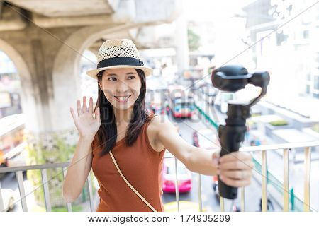 Woman holding video stabilizer to take photo at street of Bangkok