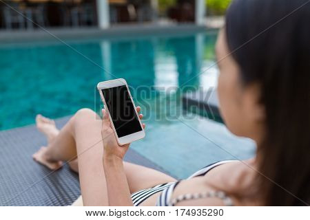 Woman use of cellphone besides the swimming pool
