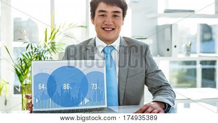 Portrait of smiling businessman using laptop in office