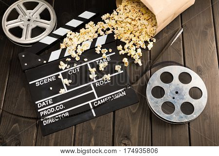 close up view of popcorn in paper container and movie clapper board on table Movie time concept