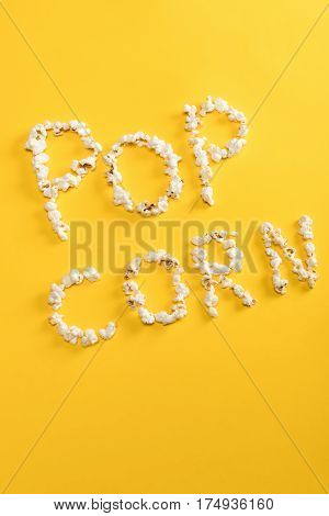 Top view of Pop corn lettering made from popcorn kernels on yellow