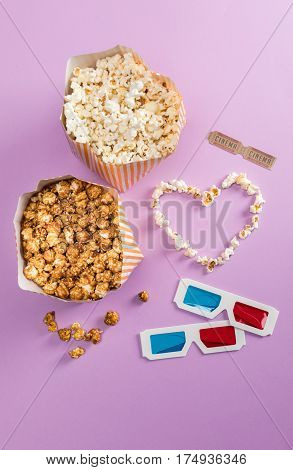 Top view of popcorn with heart symbol and 3D glasses with cinema tickets Movie time concept