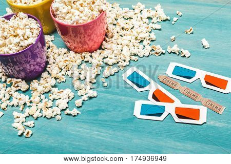 Close-up view of popcorn in bowls and 3D glasses on wooden table Movie time concept