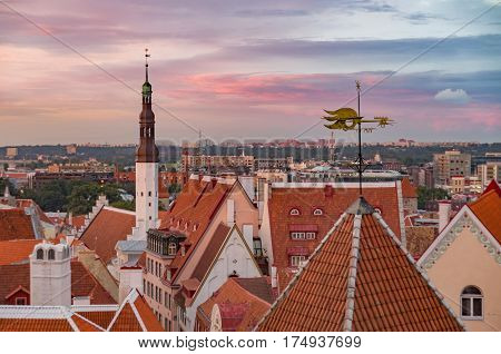 Townhall and red roofs of Old Town against wonderful sunset sky Tallinn Estonia
