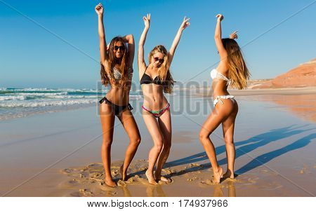 Three beautiful girls having fun on the beach