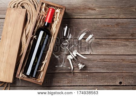 Red wine bottle and glasses on wooden table. Top view with copy space
