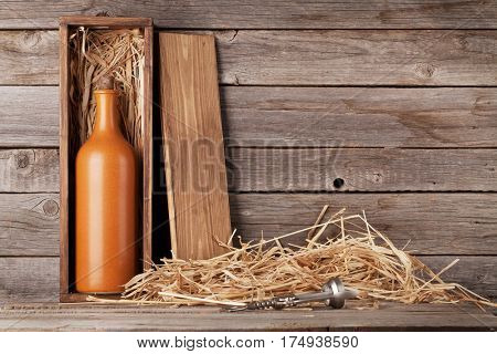 Wine bottle in box in front of wooden wall. With copy space