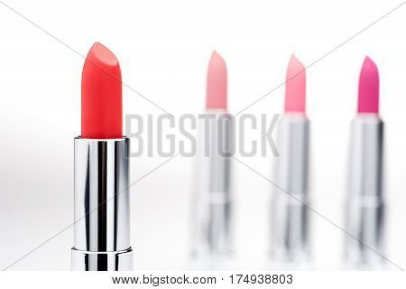 Close-up view of glamorous red lipstick with set of pink lipsticks behind