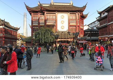 Shanghai, China - March 2, 2017: Tourists walking at sunset in the City Temple of Shanghai, in the old town. On background the Shanghai Tower