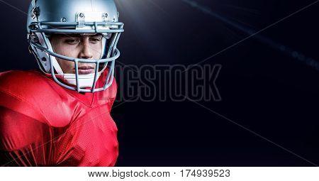 Serious american football player wearing helmet standing against black background