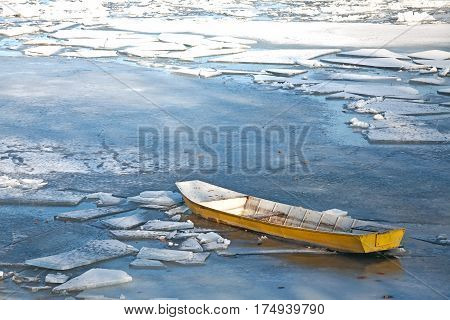 Yellow boat trapped in ice in the winter.