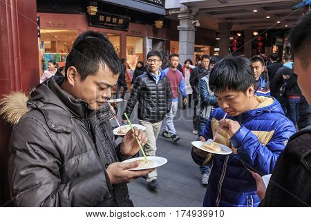 Shanghai, China - March 2, 2017: Chinese People Eating Restaurant Steamed Xiao Long Bao In The City