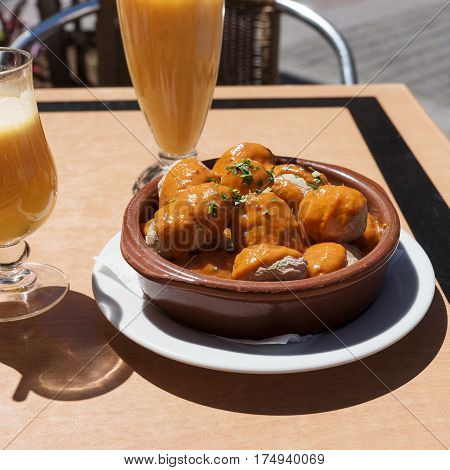 Canarian potatoes (boiled potatoes) with sauce on wooden table