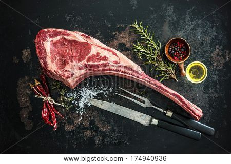 Dry aged raw tomahawk beef steak with ingredients for grilling: