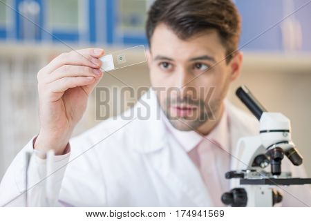 Man scientist in white coat looking at glass microscope slide in lab
