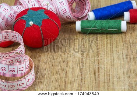 Red pincushion, tape and several threads with needle are on the light wooden background