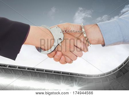 Digital composite image of business professional shaking hands with hand cuffs against sky in the background