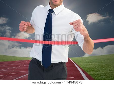 Digital composite image of a businessman winning the race on race track