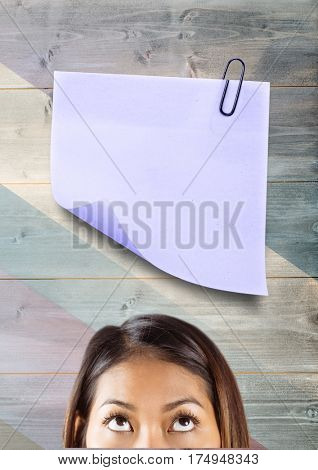 Digital composite image of a woman looking at paper attached with paper clip against wooden background